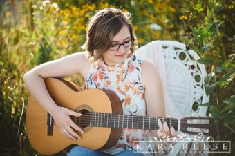 senior picture outside in field of flowers on white chair with guitar
