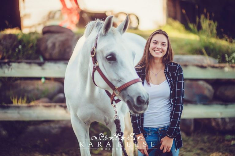 Senior girl in plaid shirt with horse outside