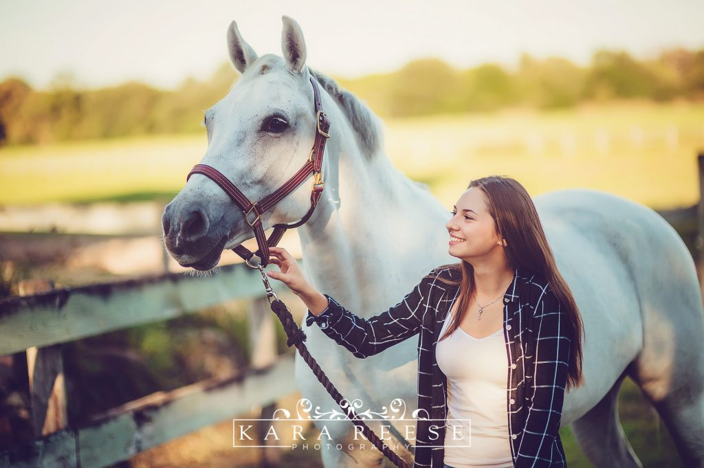high school girl outside next to white horse