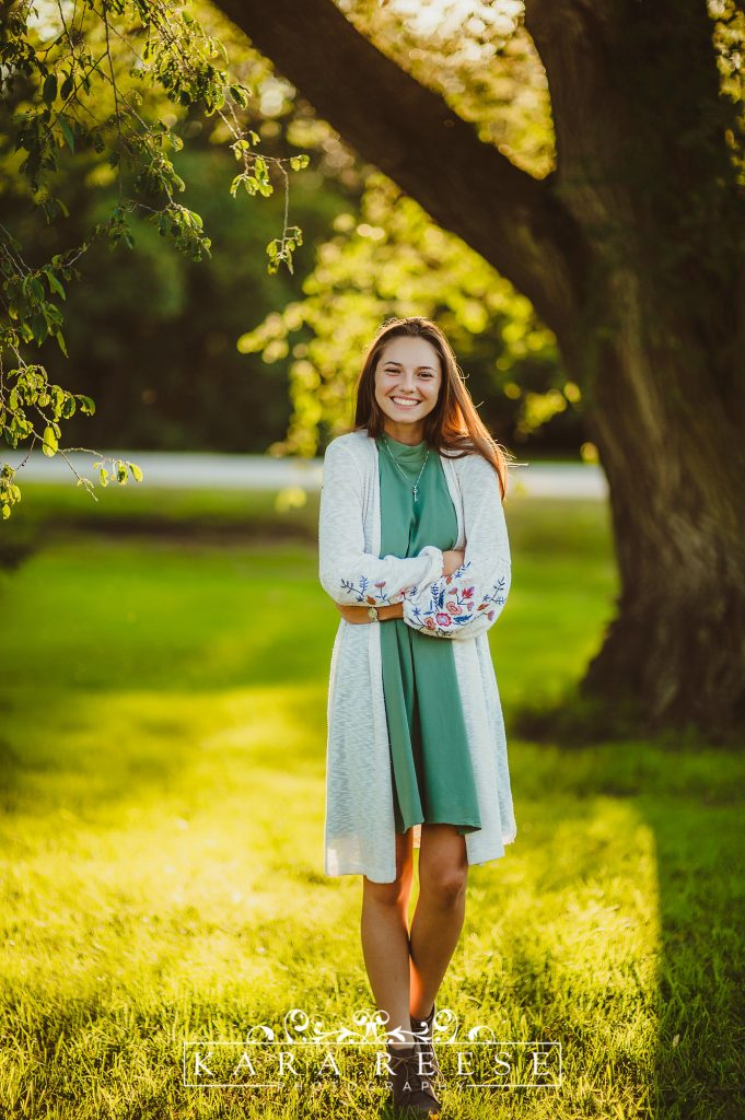 girl in green dress in white sweater outside by tree