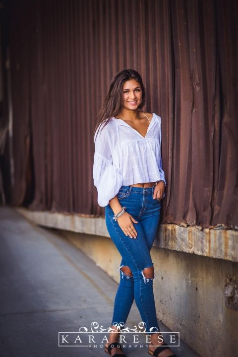 teen girl with brown hair, white shirt, and jeans in urban setting