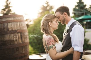 bride and groom outside by barrell at reception