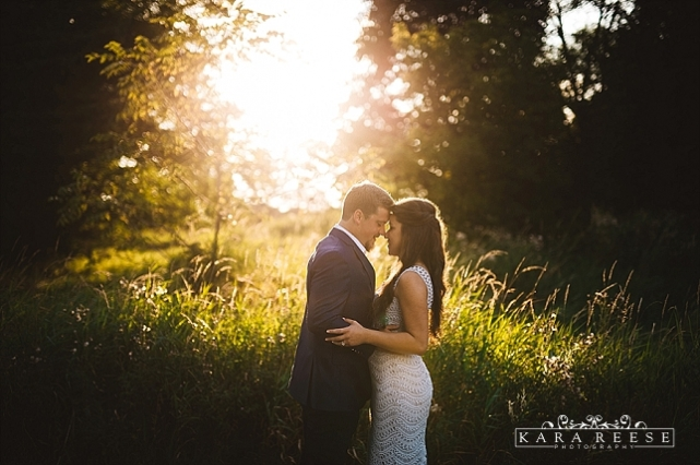 engaged couple embracing in grassy area with sun behind them