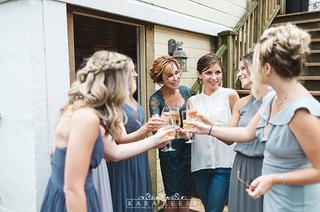 bride with bridesmaids toasting champagne